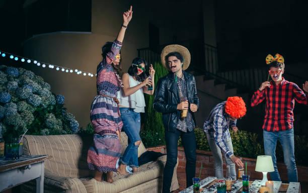 glückliche freunde tanzen und spaß mit kostümen in partei - freund kostüme stock-fotos und bilder
