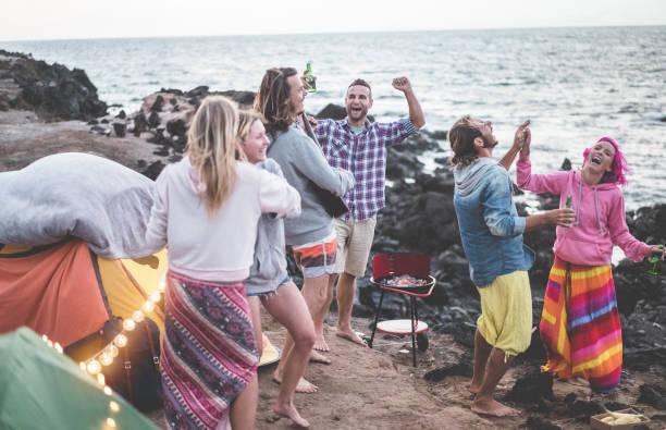 glückliche freunde tanzen und grill strand party machen - erwachsene surfer menschen spaß zusammen trinken bier und camping nächsten ozean - schwerpunkt mann mittelfläche - spaß, urlaub und freundschaft konzept - tanz camp stock-fotos und bilder