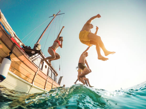 Happy friends diving from sailing boat into the sea young people picture id940945814?b=1&k=6&m=940945814&s=612x612&w=0&h=wxsigbud5fihfmwcad45acqjs7ojp3iwradu ngyl4k=