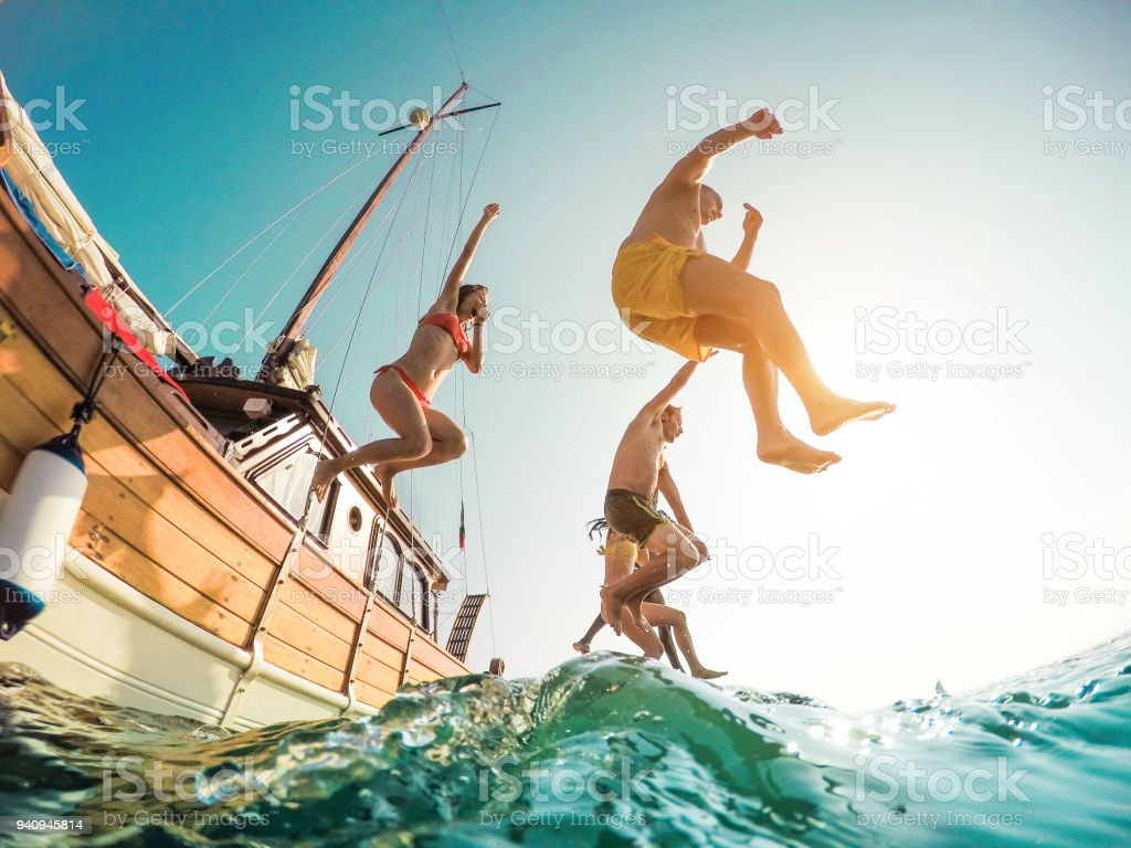 Happy friends diving from sailing boat into the sea - Young people jumping inside ocean in summer excursion day - Vacation, youth and fun concept - Main focus on left man - Fisheye lens distortion - fotografia de stock