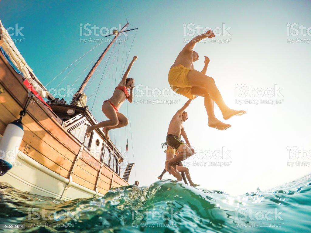 Amigos felizes, mergulhar de barco à vela o foco de Main - jovens pulando para dentro do oceano no verão excursão dia - férias, juventude e diversão conceito - mar na esquerda homem - distorção de lente olho de peixe - foto de acervo