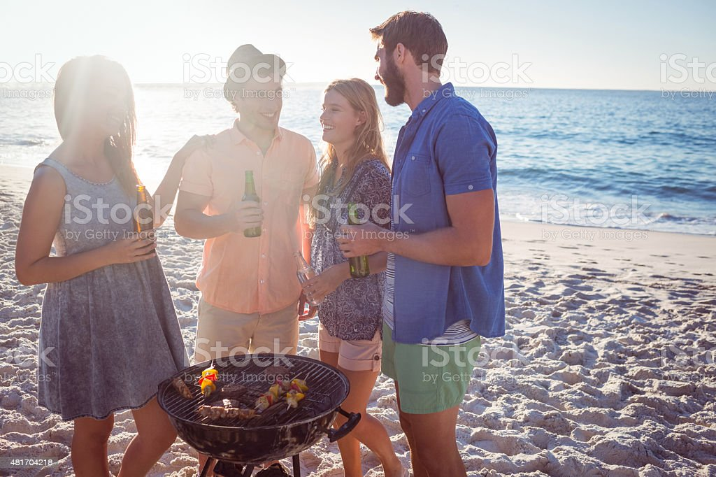 Happy friends doing barbecue and drinking beer stock photo