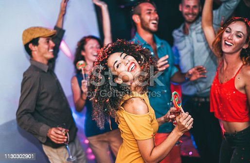 Happy friends doing party at night club - Young woman having fun with her group of mates eating candy lollipops inside disco - People, friendship, nightlife and youth holidays lifestyle