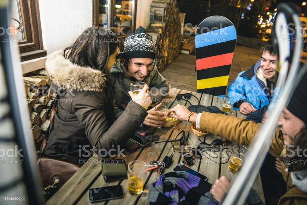 Happy friends drinking beer and eating chips at apres ski - Friendship concept with cheerful people having fun at bar restaurant resort with snow equipment - High iso image with shallow depth of field stock photo