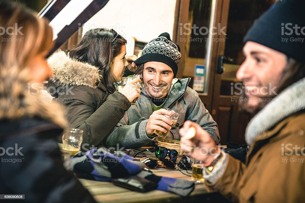 Happy friends drinking beer and eating chips by night stock photo