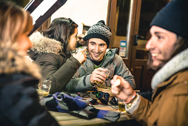 happy friends drinking beer and eating chips by night - station de ski photos et images de collection
