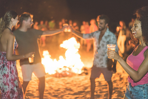 Happy friends drinking beer at beach festival with bonfire in background - Young people having fun summer vacation - Youth,holidays and party concept - Soft focus on afro girl hand glass - Warm filter