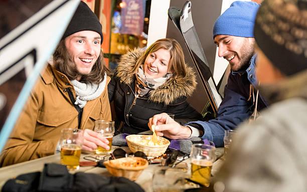 happy friends drinking beer having fun at ski resort chalet - station de ski photos et images de collection