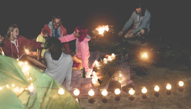 glückliche freunde trinken bier auf dem campingplatz mit vintage lichter nächste lagerfeuer im freien - glückliche menschen, die spaß im urlaub ferien - fokus auf surfbrett - freundschaft und alternative party konzept - tanz camp stock-fotos und bilder
