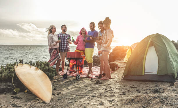 Happy friends drinking beers at camping barbecue picnic next to the ocean - Surfers people having fun and laughing together - Main focus on right guys - Travel, vacation and friendship concept stock photo