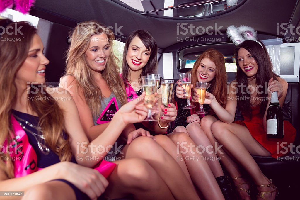 Happy friends drinking champagne in limousine stock photo