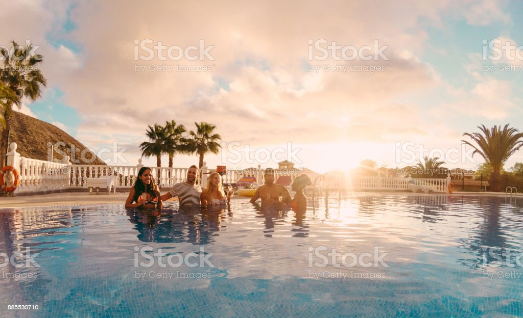 Happy friends drinking champagne in pool party at sunset - Rich people having fun in exclusive tropical vacation - Holiday and friendship concept - Main focus on left guys - Original sun colors tones stock photo