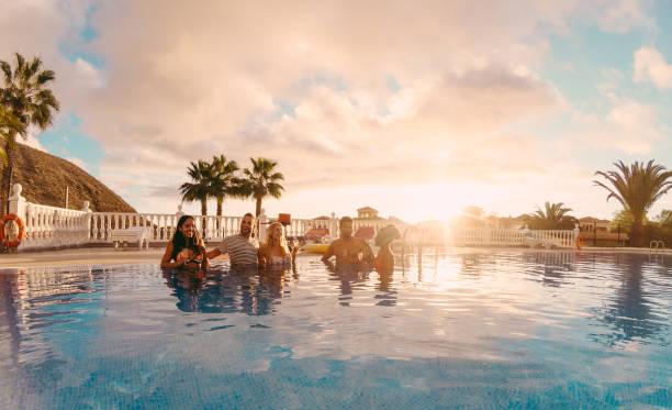 glückliche freunde trinken champagner im pool party im sonnenuntergang - reiche leute spaß in exklusiven tropischen urlaub - urlaub und freundschaft konzept - schwerpunkt linken jungs - original sonne farbtöne - griechische partyspeisen stock-fotos und bilder