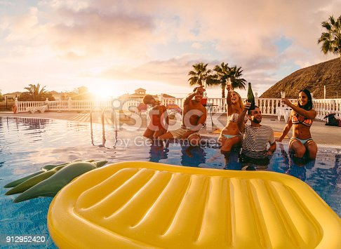istock Happy friends drinking champagne in pool party at sunset - Rich people having fun in exclusive tropical vacation - Holiday and friendship concept - Main focus on right guys - Original sun colors tones 912952420
