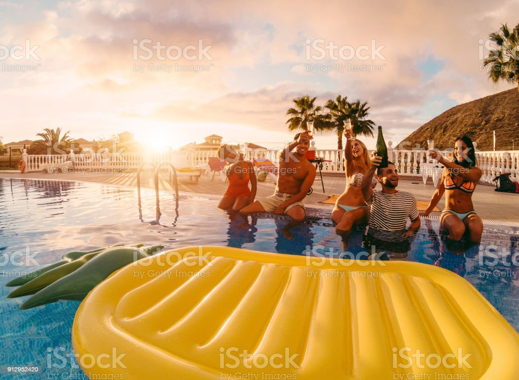 Happy friends drinking champagne in pool party at sunset - Rich people having fun in exclusive tropical vacation - Holiday and friendship concept - Main focus on right guys - Original sun colors tones stock photo