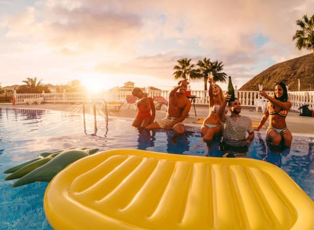 glückliche freunde trinken champagner im pool party im sonnenuntergang - reiche leute spaß in exklusiven tropischen urlaub - urlaub und freundschaft konzept - schwerpunkt recht jungs - original sonne farbtöne - griechische partyspeisen stock-fotos und bilder