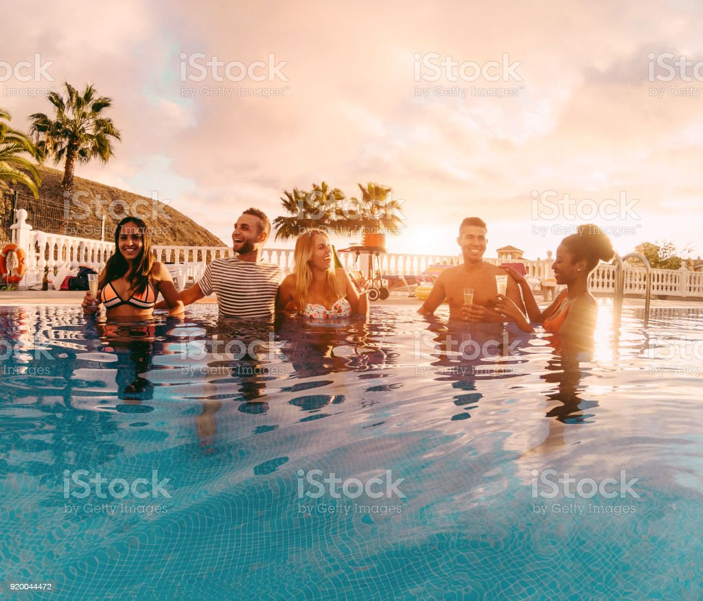 Happy friends drinking champagne in pool party at sunset - Rich people having fun in exclusive tropical vacation - Holiday, youth lifestyle and friendship concept - Main focus on left guys stock photo