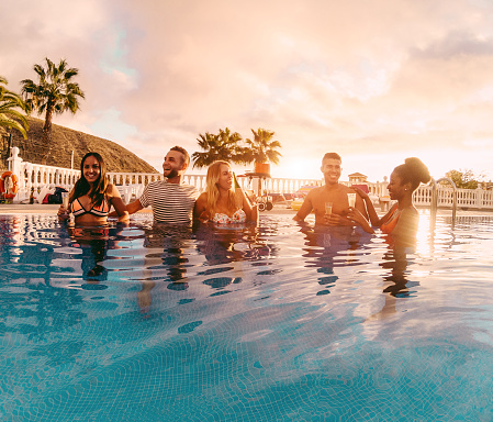 Happy Friends Drinking Champagne In Pool Party At Sunset Rich People Having Fun In Exclusive Tropical Vacation Holiday Youth Lifestyle And Friendship Concept Main Focus On Left Guys Stock Photo - Download Image Now