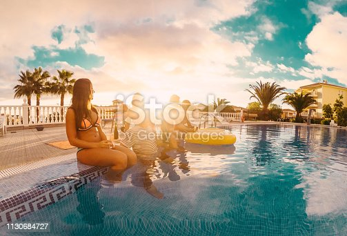 istock Happy friends drinking champagne in pool party at sunset - Young people having fun in exclusive tropical vacation - Summer holiday, youth lifestyle and friendship concept - Tilted horizon composition 1130684727