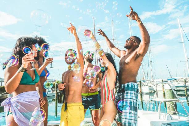 happy vrienden drinken champagne in de zomer boat party-jonge mensen die plezier vieren en dansen-jeugd lifestyle, exclusieve fest en vakantieconcept-belangrijkste focus op het centrum jongens gezichten - strandfeest stockfoto's en -beelden