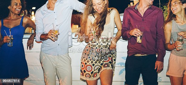 Happy friends drinking cocktails at beach party outdoor - Young millennials people having fun at weekend summer night lounge club - Youth lifestyle and nightlife concept - Main focus on center girl