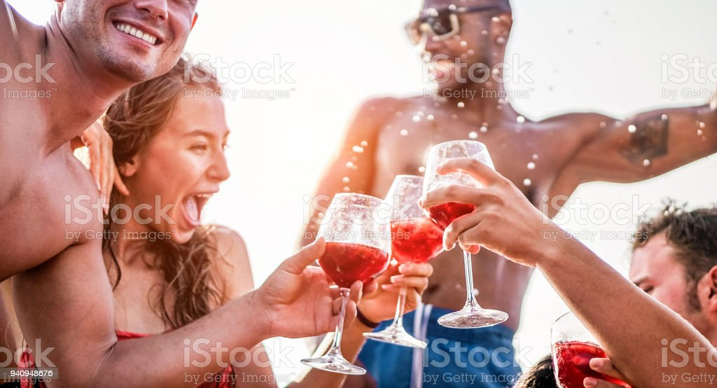 Happy friends drinking sangria wine at exclusive boat party - Young people having fun in summer vacation - Focus on left man hand glass - Travel, friendship, holidays and youth lifestyle concept stock photo