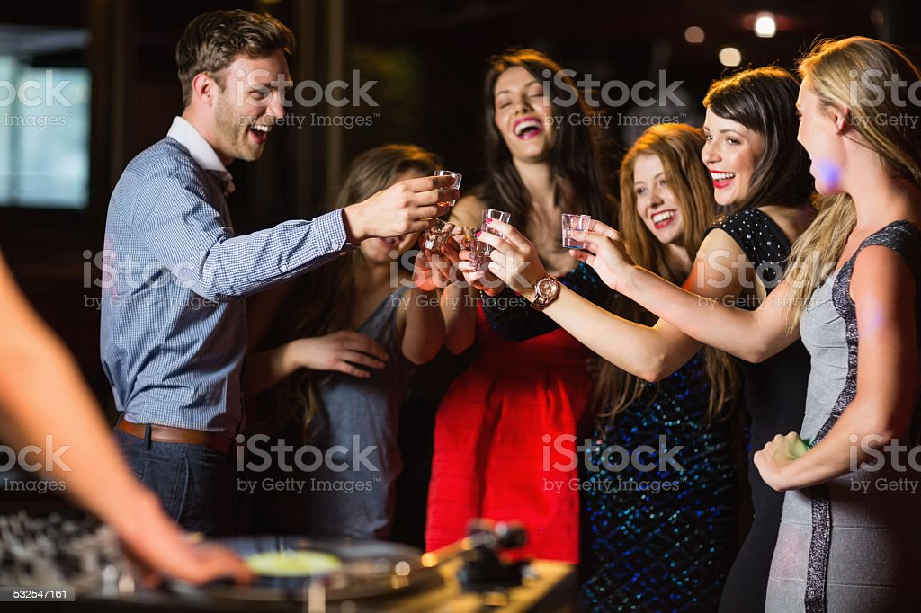 Happy friends drinking shots by the dj booth stock photo