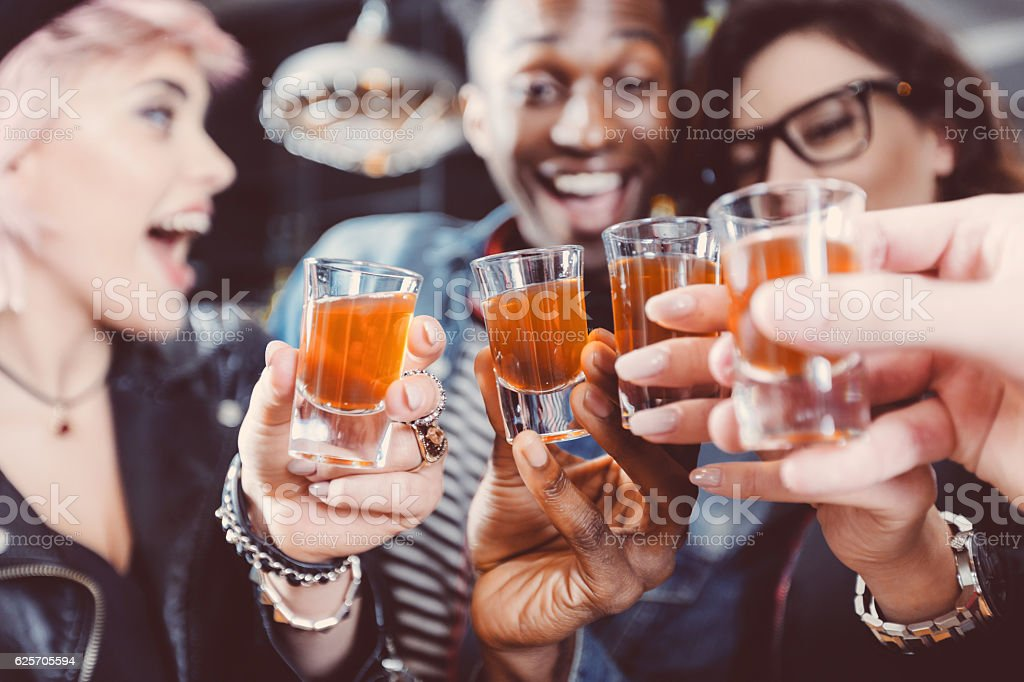 Happy friends drinking shots stock photo