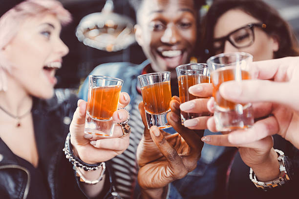 happy friends drinking shots - alcohol stock photos and pictures