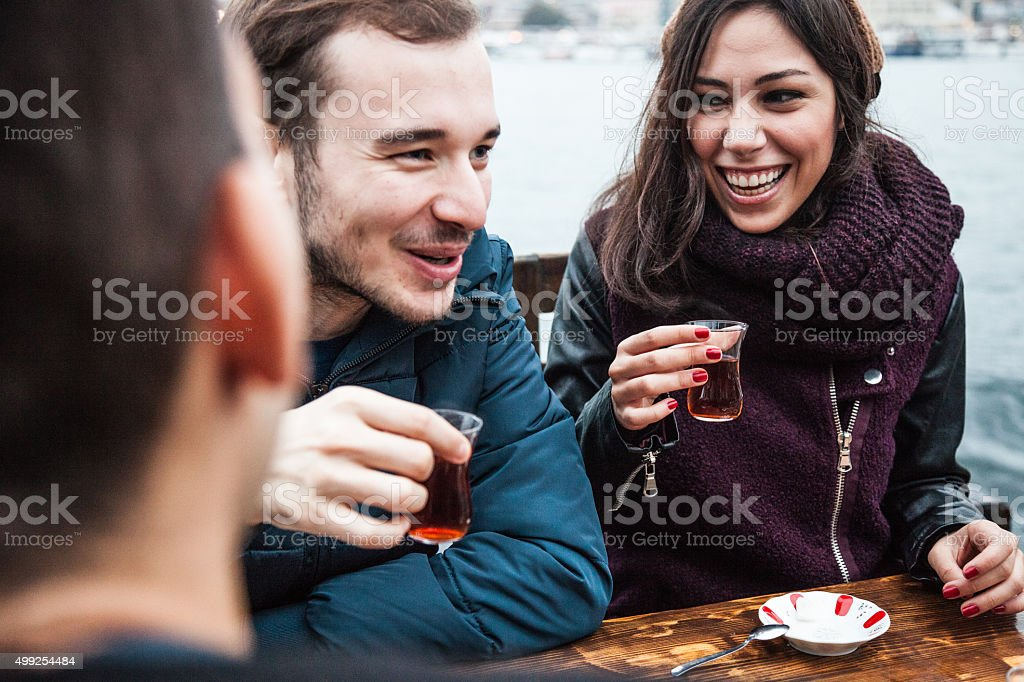 Happy friends drinking tea in a cafe stock photo