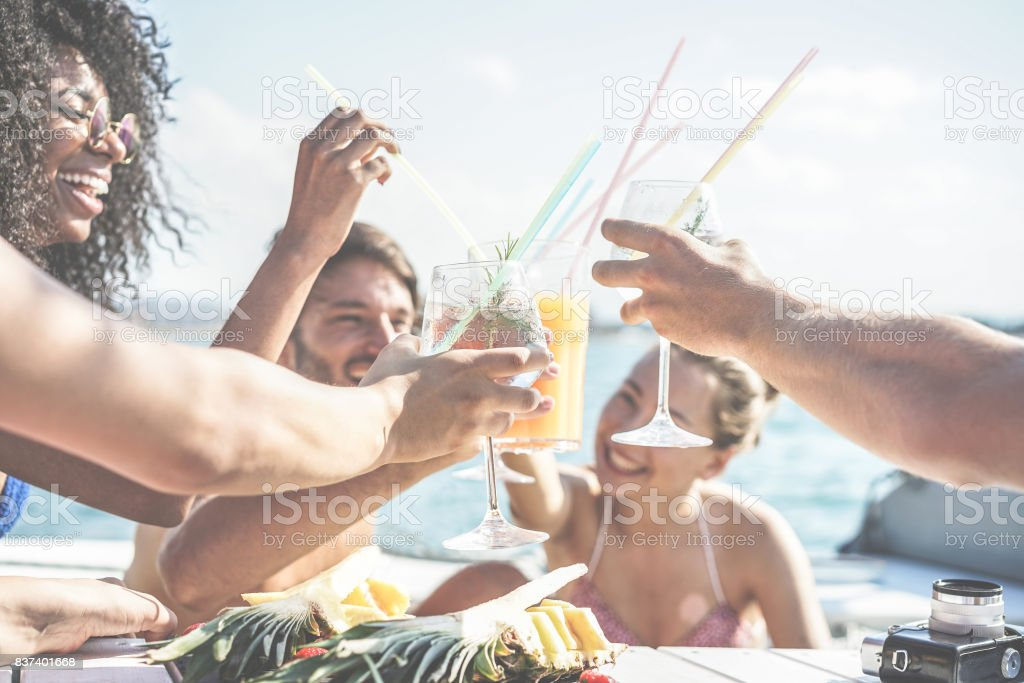 Happy friends drinking tropical cocktails at boat party and eating pineapple - Young people having fun in sea excursion - Youth and summer concept - Main focus on left bottom hand glass - Retro filter stock photo