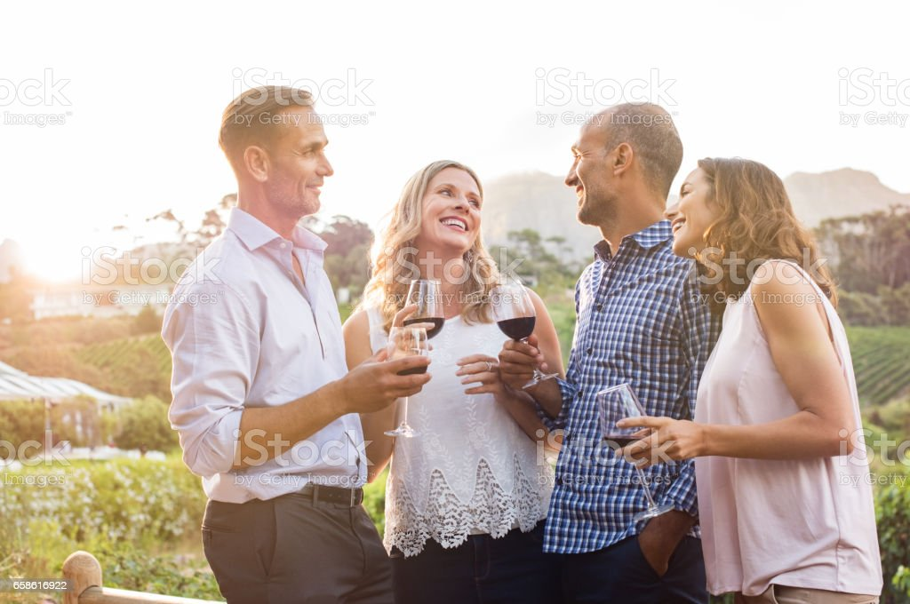 Happy friends drinking wine stock photo