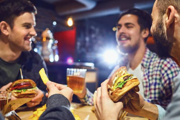 Glückliche Freunde essen Burger, trinken in einer Bar Bier. – Foto