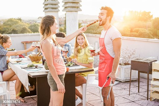 istock Happy friends eating and drinking red wine at barbecue party - Trendy people grilling and having fun at bbq dinner outdoor - Main focus on right man face - Youth lifestyle, fun and friendship concept 908651474