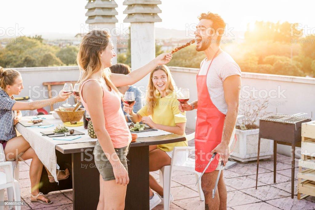 Heureux amis, manger et boire du vin rouge au barbecue party - Trendy personnes griller et de s'amuser chez bbq dîner en plein air - objectif principal sur le visage de l'homme - jeunesse mode de vie, de plaisir et d'amitié concept - Photo