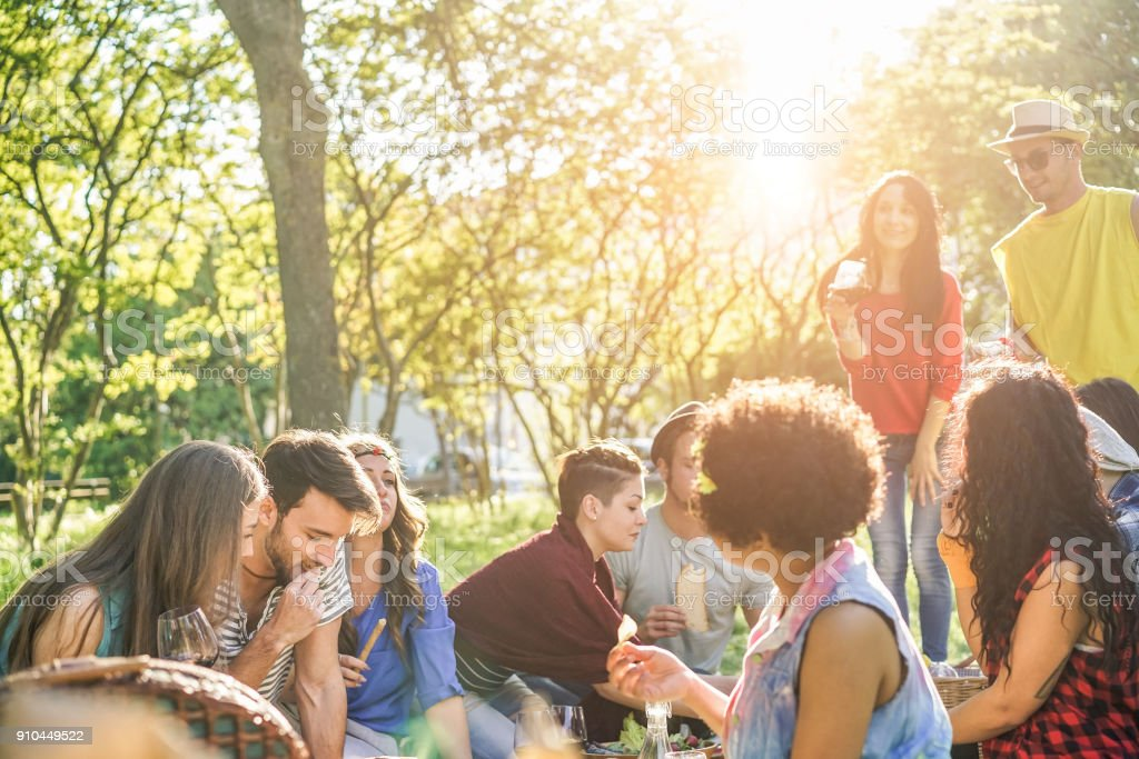 Happy friends eating and drinking red wine at picnic party outdoor - Young trendy people having fun together at summer dinner - Taste, friendship and youth lifestyle concept - Focus on two left guys stock photo