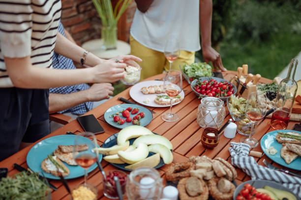 Happy friends eating outdoors and having fun stock photo