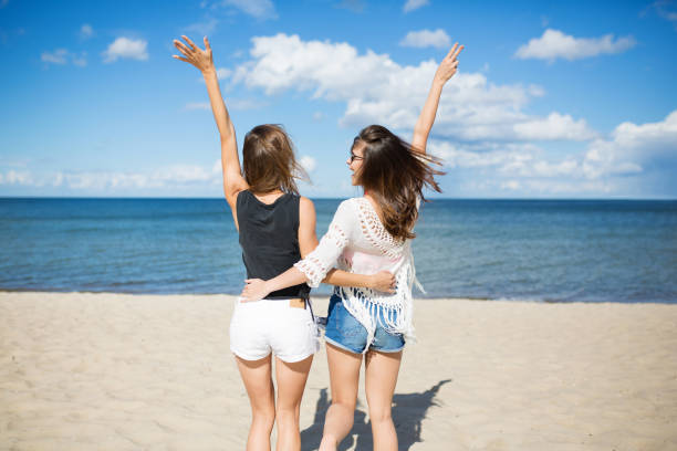 Happy friends embracing each other raising hands on beach stock photo