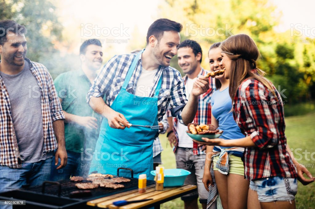 Happy friends enjoying barbecue party stock photo
