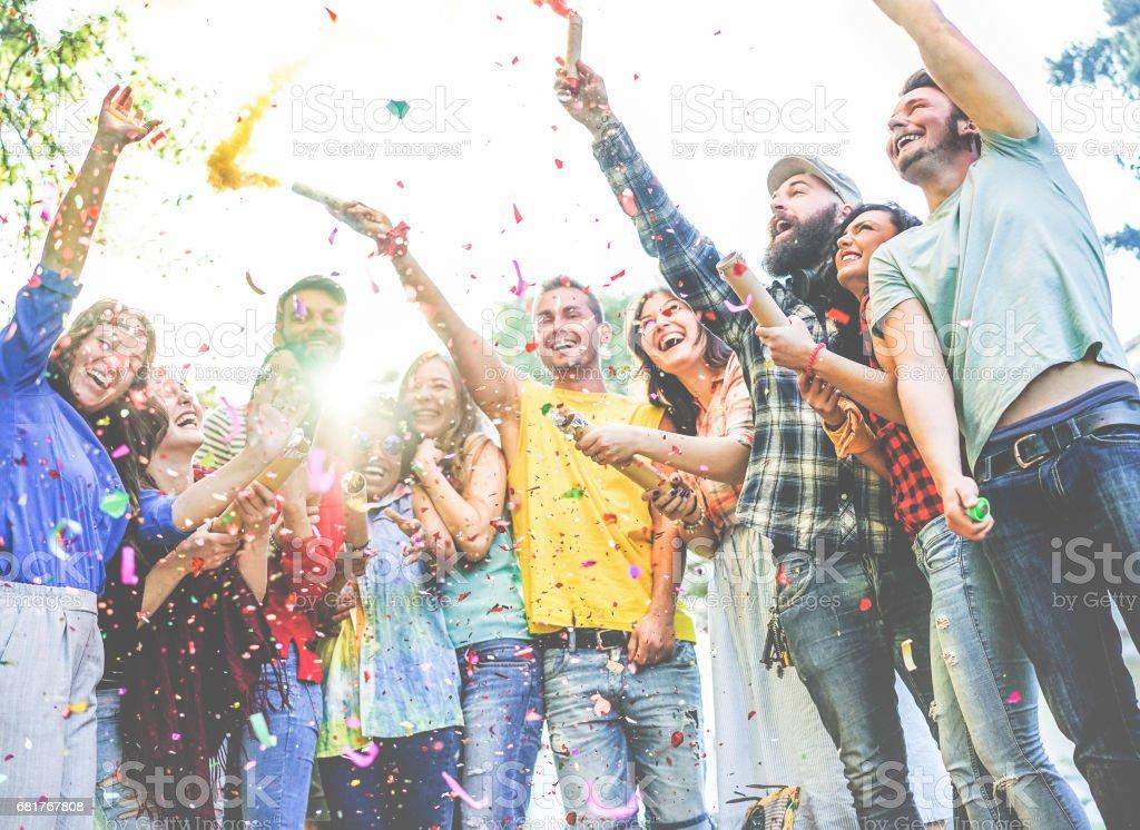Heureux amis appréciant parti, jetant des confettis et en utilisant des bombes fumigènes couleurs à fête en plein air photo libre de droits