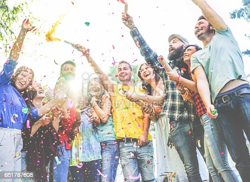 istock Happy friends enjoying party,throwing confetti and using smoke bombs colors at party outdoor 681767808
