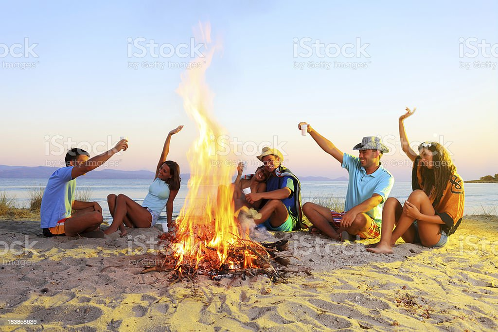 Happy friends enjoying, sitting next to the campfire. royalty-free stock photo