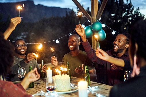 Happy friends holding glowing sparklers at table. Men and women are celebrating birthday in balcony. They are having fun in party at night.