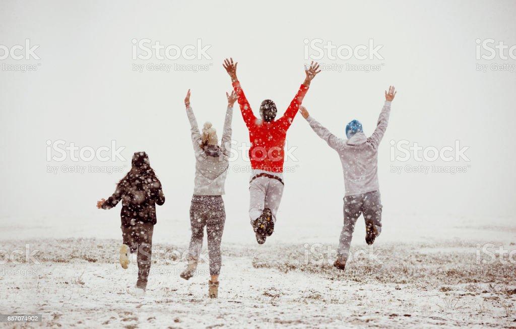 Amistad amigos feliz correr saltar primera nieve - foto de stock
