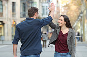 Happy friends giving high five in the street