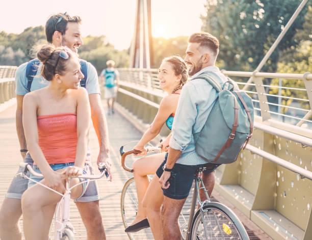 glückliche freunde gehen mit fahrrädern am stadtpark - junge leute, die spaß an sonnigen tagen - jugend, freundschaft und gesunden lifestyle-konzept - konzentrieren sich auf richtige mädchen gesicht - sonne farbtöne filtern - studieren in deutschland stock-fotos und bilder