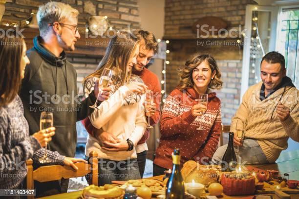 Happy Friends Groep Viert Kerstfeest Met Witte Wijn En Zoete Gerechten Tijdens Het Diner Avondmaalwinter Vakantie Concept Met Jonge Mensen Genieten Van Tijd En Plezier Samen Etenwarm Filter Stockfoto en meer beelden van 2019