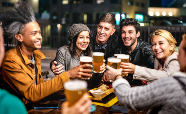Happy friends group drinking beer at brewery bar out doors - Friendship lifestyle concept with young people enjoying time together at open air pub - Selective focus on girl with hat stock photo