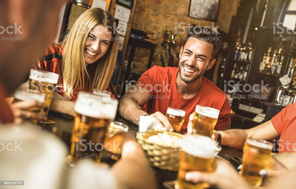 Happy friends group drinking beer at brewery bar restaurant - Friendship concept with young people enjoying time together and having genuine fun at cool vintage pub - Focus on guy - High iso image stock photo