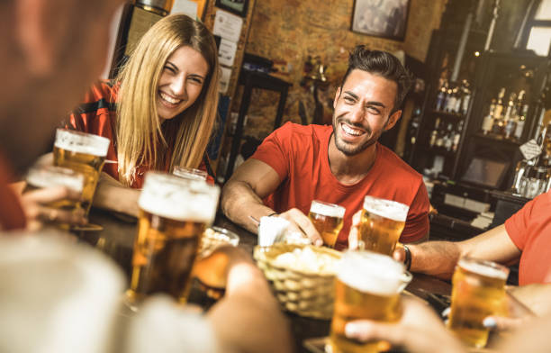 happy friends group drinking beer at brewery bar restaurant - friendship concept with young people enjoying time together and having genuine fun at cool vintage pub - focus on guy - high iso image - german culture stock pictures, royalty-free photos & images